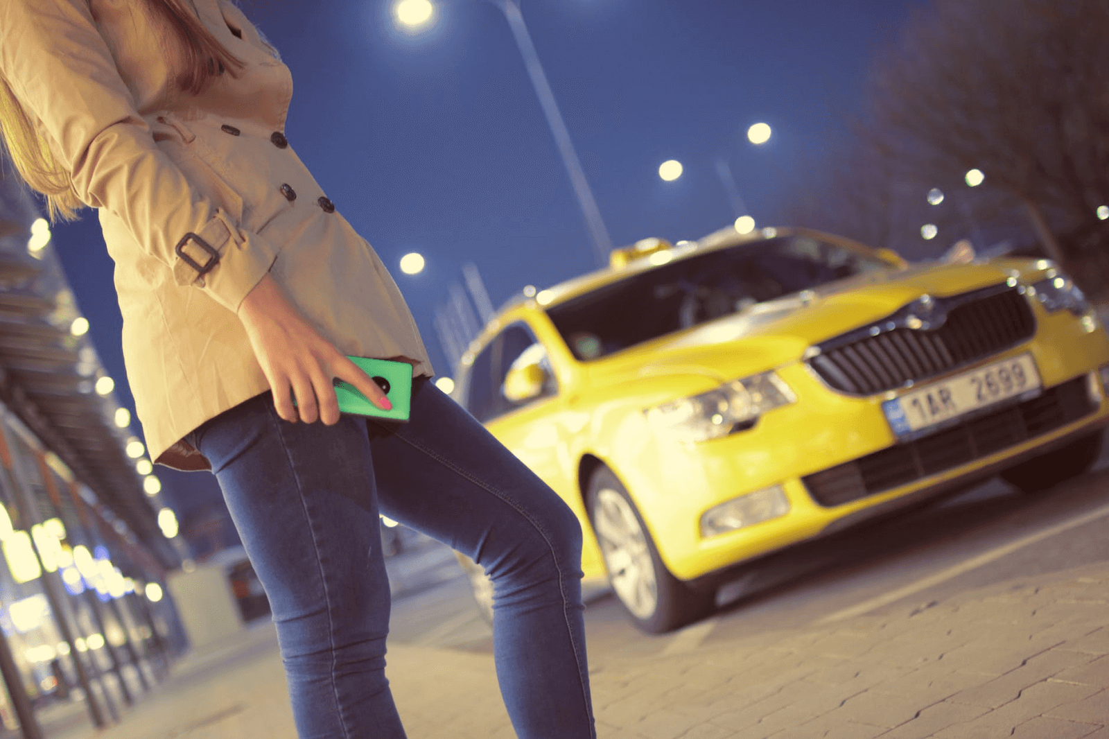 Woman holding phone to call Uber in front of taxi