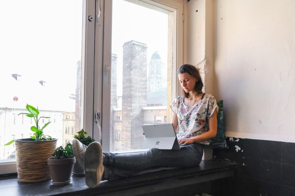 Jobs for introverts: A woman sits in a window and works on her laptop