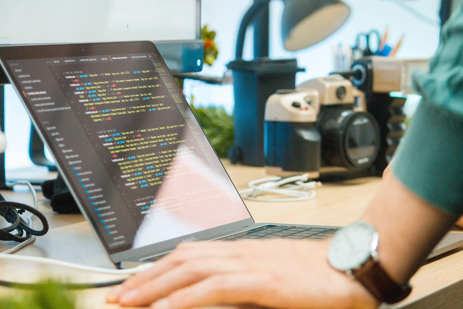 How to become a software developer: A hand leans on a desk in front of a laptop screen covered in code