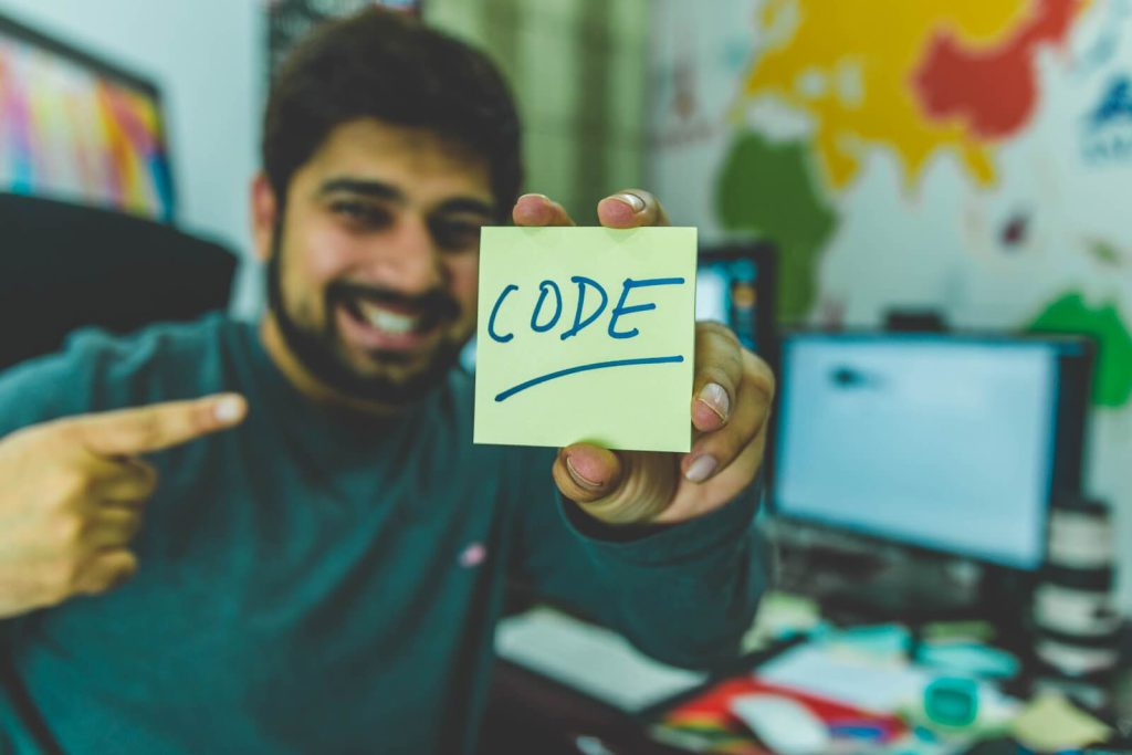 """How to become a software developer: A man holds a sticky note that says """"CODE"""""""