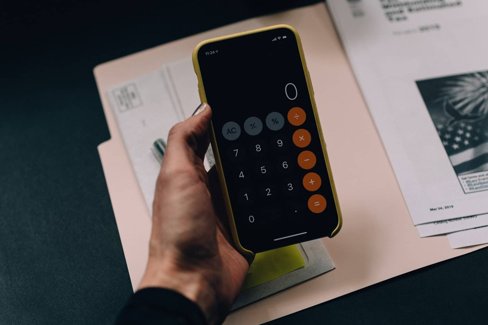 How to calculate profit margin: a hand holds a calculator over file folders