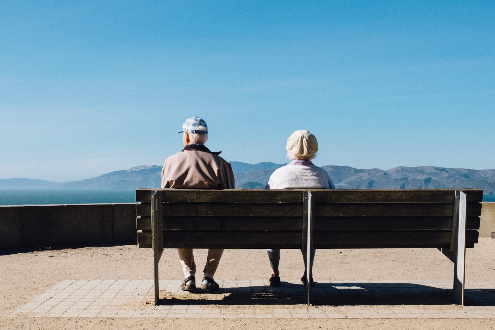 Elderly couple sitting on a bench looking out at mountains