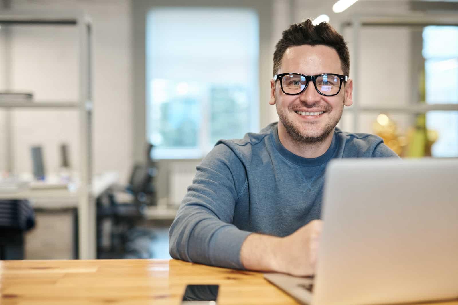 man smiling at computer