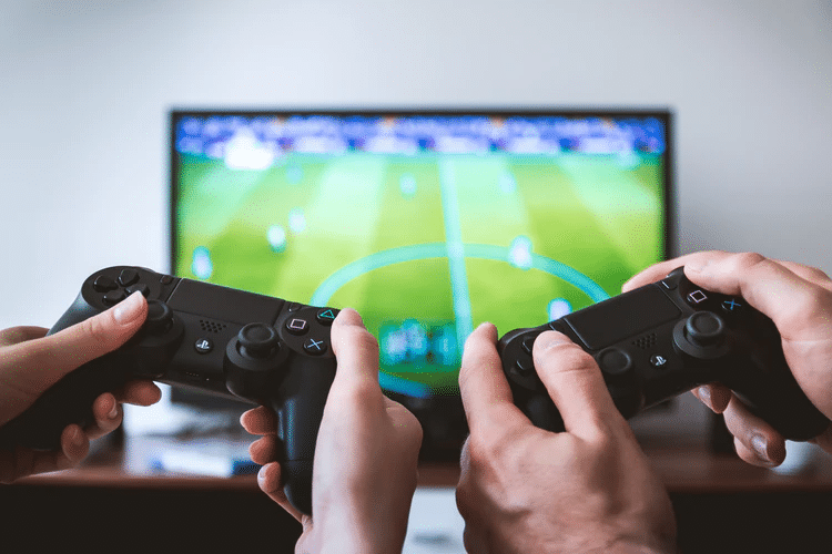 two people holding game controllers in front of screen