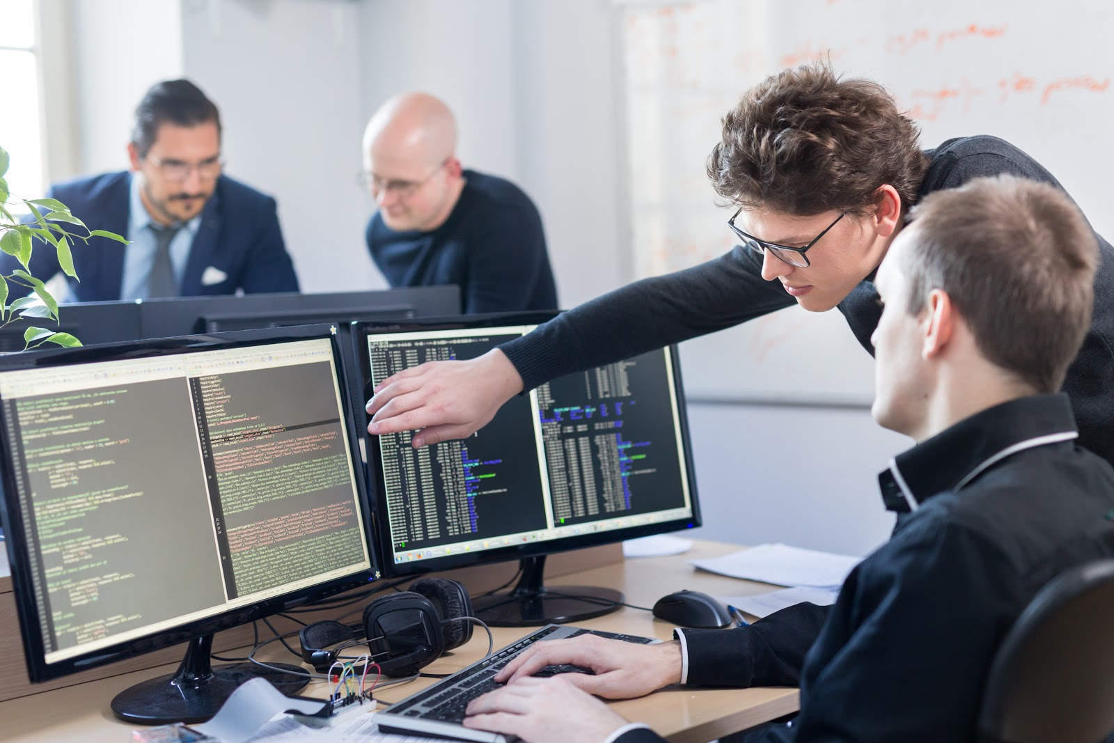 What is Jira: Programmers and Developers programming on a desktop computer